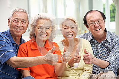 Group Of Senior Chinese Friends Relaxing At Home