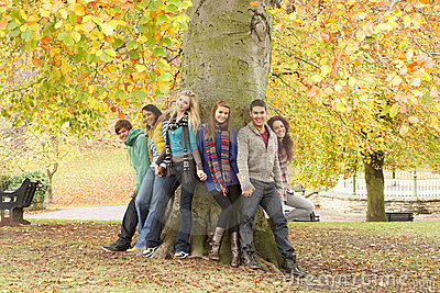 Group Of Six Teenage Friends Leaning Against Tree