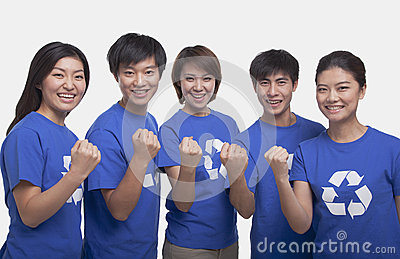 Group of smiling and happy people wearing recycling symbol t-shirts standing in a row with raised fists, studio shot
