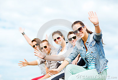 Group of teenagers waving hands
