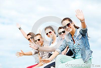 Group of teenagers waving hands