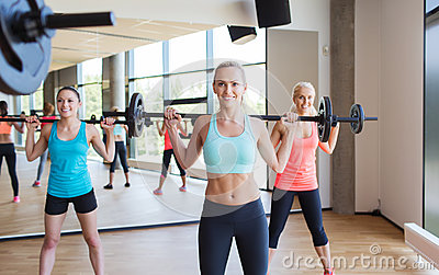 Group of women excercising with bars in gym Stock Photo