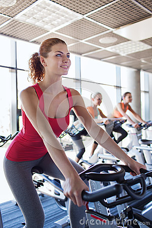 Group of women riding on exercise bike in gym Stock Photo