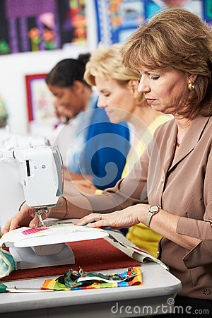 Group Of Women Using Electric Sewing Machines In class