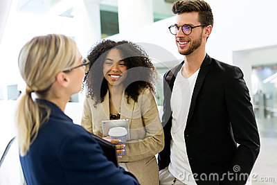 Group of young business people talking in a hallway of the company. Stock Photo