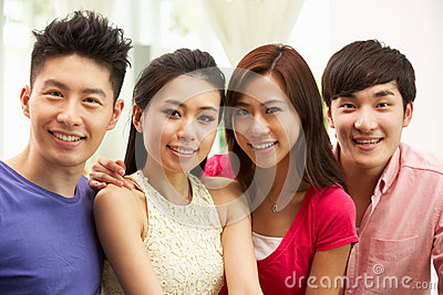 Group Of Young Chinese Friends Relaxing At Home