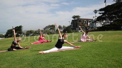 group of young people practicing yoga on the seaside