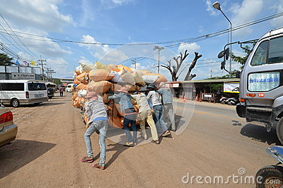 A group of young people pushing a cart overloaded bags