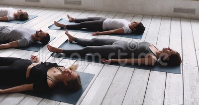 group of people practicing yoga doing corpse dead body
