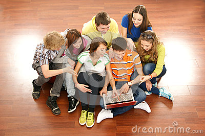 A group of young teenagers looking at the laptop