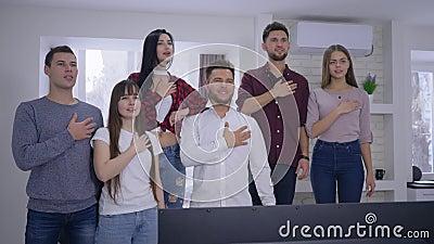 Groupe de supporters d'amis chantant l'hymne national avant d'observer le championnat de sports à la TV ensemble à la maison banque de vidéos