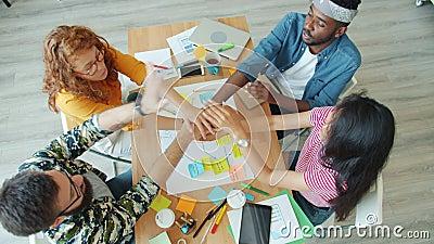 Groupe multiracial réalisant un collage au bureau travaillant pour un projet jouissant d'un travail d'équipe banque de vidéos