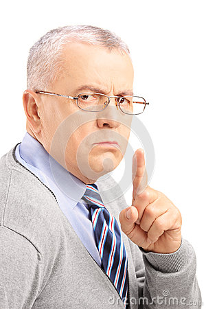 Grumpy mature man gesturing silence with a finger