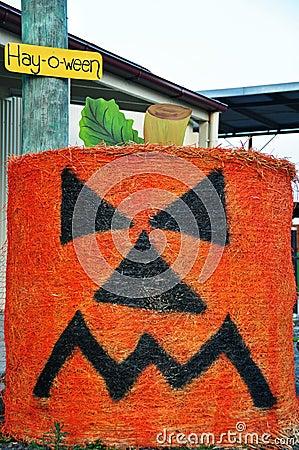 Grumpy pumpkin face halloween round hay bale