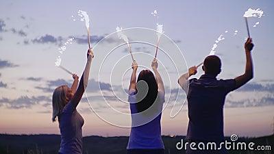 Grupa przyjaciele ma zabawę z fajerwerkami lub Bengalia światłami zwolnionego tempa wideo zdjęcie wideo