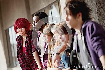 Grupo de adolescentes novos que olha fixamente na distância.
