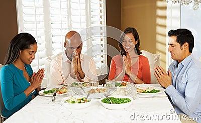 Grupo de amigos que dicen tolerancia antes de comida en casa