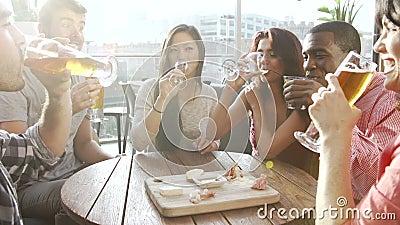 Grupo de amigos que gozan de la bebida y del bocado en barra del tejado almacen de video