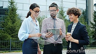 Grupo de colegas que olham para a tela de tablet conversando fora do centro de negócios da cidade filme