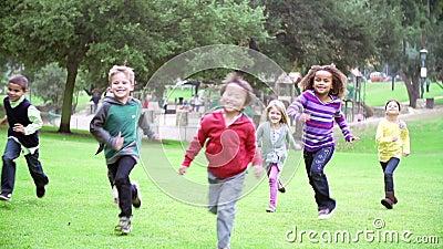 Grupo de crianças que correm para a câmera no movimento lento filme