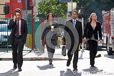Grupo de empresarios que cruzan la calle