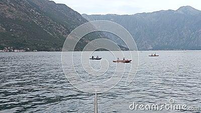 Grupo de enfileirar os povos que navegam na água calma filme