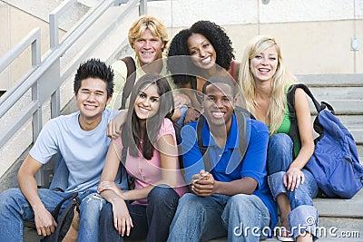 Grupo de estudantes universitários que sentam-se em etapas