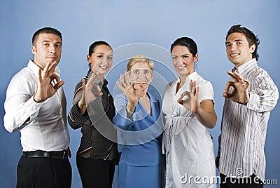 Grupo de executivos que mostram o sinal aprovado