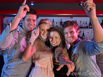Grupo de gente joven que se divierte en barra ocupada