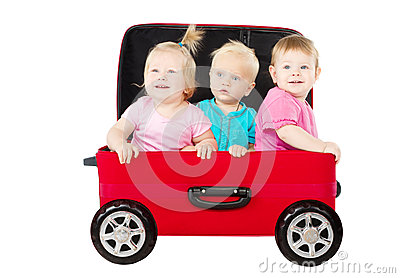 Grupo de miúdos que conduzem no carro da mala de viagem