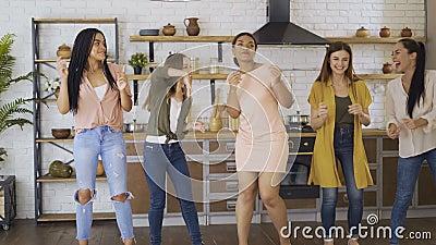 Grupo de raças mistas de 5 amigos se divertindo na cozinha. as meninas dançam e cantam enquanto cozinham 4K filme