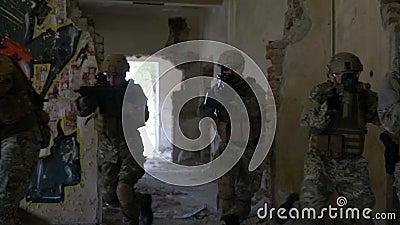 Grupo de soldados que se mueven rápidamente a través del edificio arruinado en búsqueda y la operación de rescate almacen de video