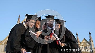 Grupo multi-étnico de estudantes licenciados que se candidatam a selfie filme