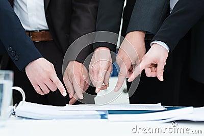 Grupp av businesspeople som pekar till ett dokument