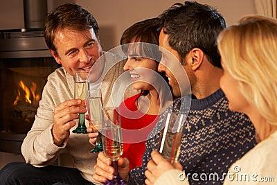 Grupp av medelåldriga par med champagne