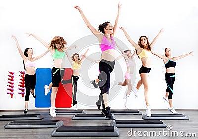 Gruppe Frauen, die Aerobics auf Stepper tun