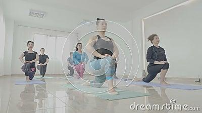 Gruppe mittlere Greisinnen, die ihre Körper während einer Yogaklassensitzung in einem Eignungsstudio tonen - stock footage