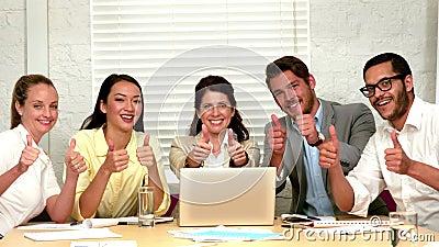 Gruppo casuale di affari che mostra i pollici fino alla macchina fotografica nel corso della riunione video d archivio