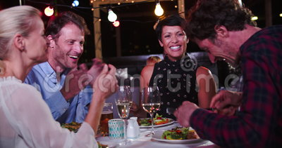 Gruppo di amici maturi che godono del pasto al ristorante del tetto