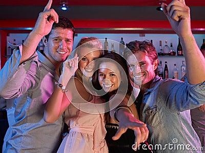 Gruppo di giovani che hanno divertimento in barra occupata