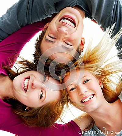 Gruppo di giovani felici nel cerchio alla spiaggia