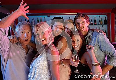 Gruppo di persone che hanno divertimento in barra occupata