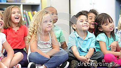 Gruppo di scolari elementari di età che si siedono sul pavimento video d archivio