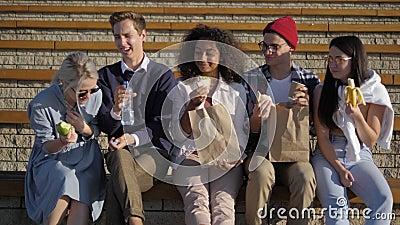 Gruppo di studenti affamati che pranzano seduti sulle scale stock footage