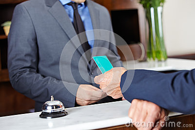 Guest giving key card to hotel receptionist