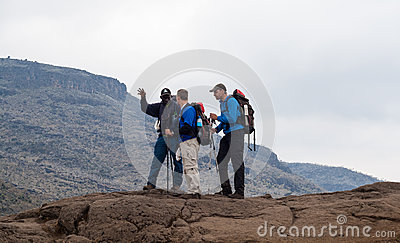 Guide instructs hiking tourists on mountain Editorial Photography