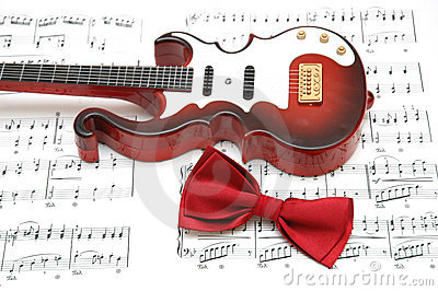 Guitar and bow tie over the sheet of printed music