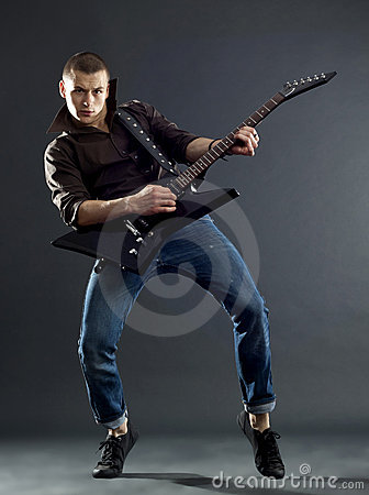 Guitar player isolated against dark background