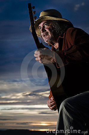 Guitar player with straw hat  in dramatic lighting