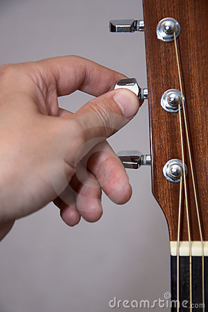 Guitarist hand tuning acoustic guitar